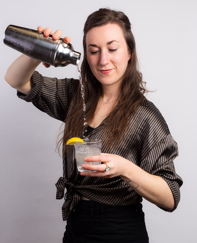 Woman pouring cocktail during virtual team building mixology class