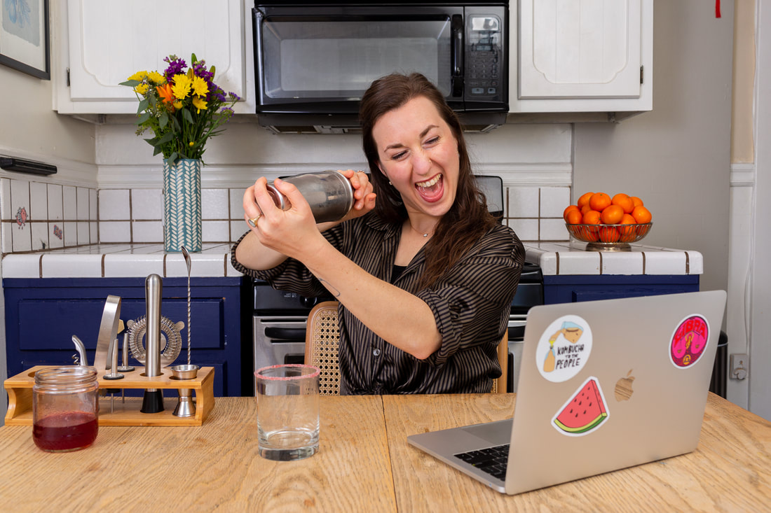 Woman teaching virtual corporate happy hour on a computer in a kitchen