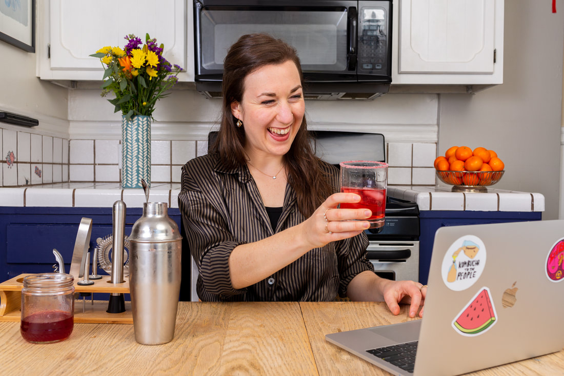 Woman teaching virtual corporate mixology class on computer in kitchen