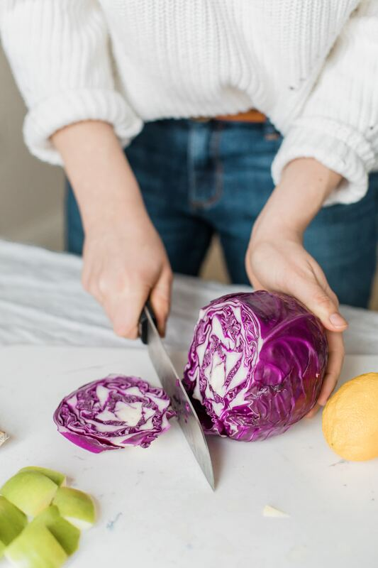 person holding half of cut cabbage for sauerkraut