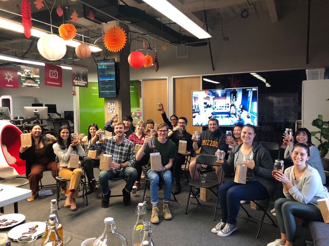 Group of people holding kombucha scoby in jars attending a corporate kombucha class